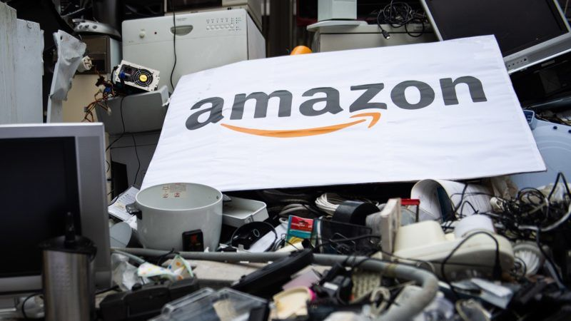 A placard with the logo of US online retailer Amazon is seen on top of trashed appliances that have been dumped by activists of French NGOs 'Les Amis de la Terre' (Friends of the Earth) and ANV Cop21 in front of the French headquarters of Amazon on November 23, 2018 in Clichy, northwest of Paris, during a protest against the company and on the first day of the Black Friday sales. (Photo by Julie SEBADELHA / AFP)