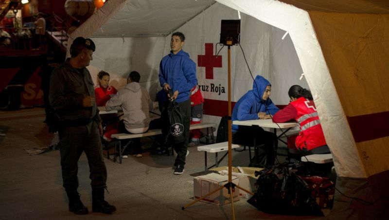 Migrants are attended by members of the Red Cross at Algeciras' harbour on November 27, 2018 after their rescue off the Spanish coast. - The onset of autumn, with the cold, storms and fog, has not stopped migrants from crossing the Mediterranean from Morocco to Spain, a journey that has this year claimed the lives of hundreds of youths. From the heights of Tarifa, veteran sailors work in shifts behind radar screens at the rescue service command centre monitoring the Strait of Gibraltar, through which 100,000 ships transit every year. (Photo by JORGE GUERRERO / AFP)