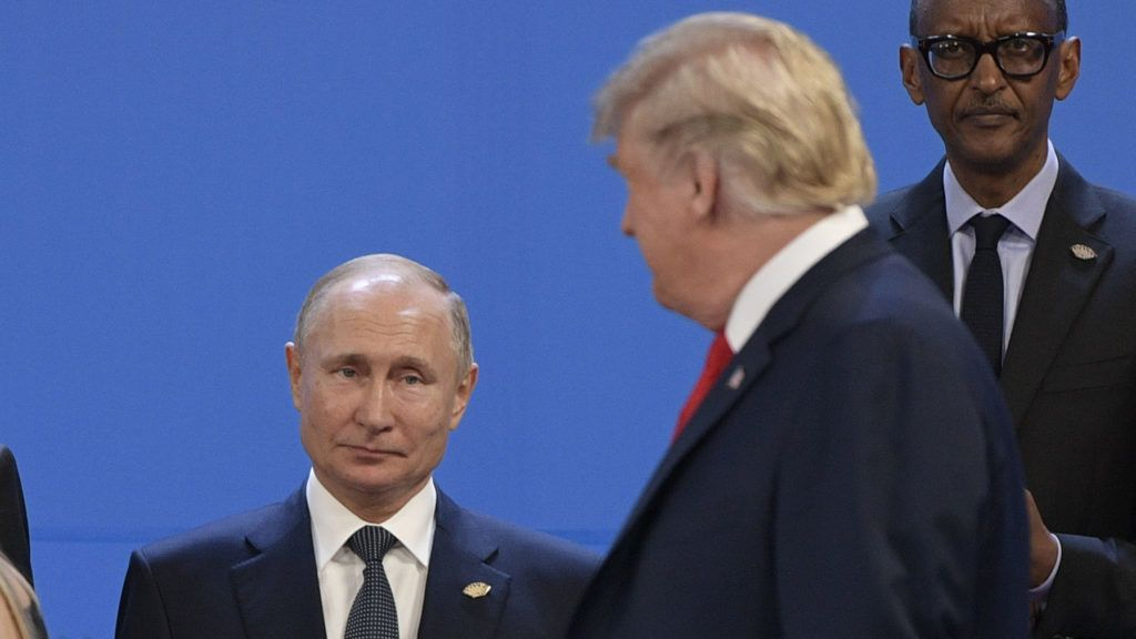 US President Donald Trump(R), looks at Russia's President Vladimir Putin as they take place for a family photo, during the G20 Leaders' Summit in Buenos Aires, on November 30, 2018. - Global leaders gather in the Argentine capital for a two-day G20 summit beginning on Friday likely to be dominated by simmering international tensions over trade. (Photo by Juan MABROMATA / AFP)