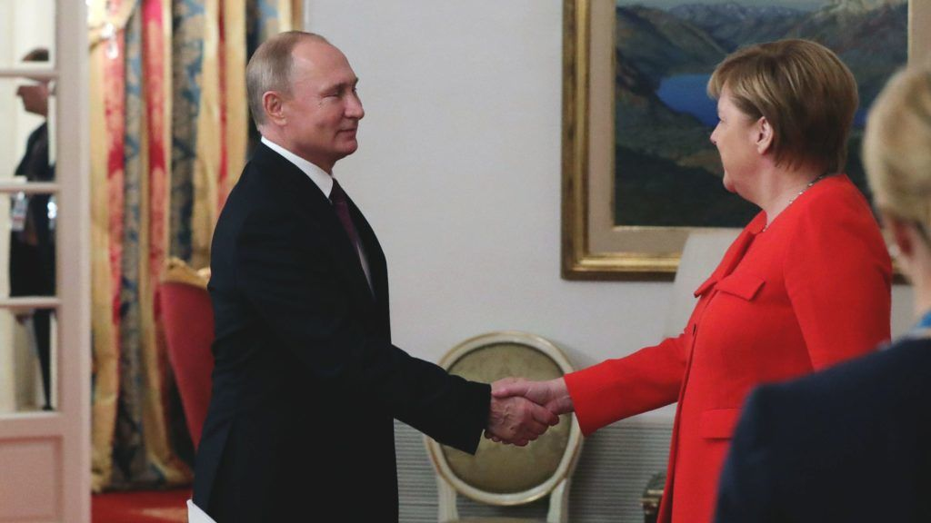 Russia's President Vladimir Putin (L) and Germany's Chancellor Angela Merkel shake hands during a bilateral meeting in the sidelines of the G20 Leaders' Summit in Buenos Aires, on December 01, 2018. - The leaders of countries representing four-fifths of the global economy opened a two-day meeting in Argentina facing the deepest fractures since the first G20 summit convened 10 years ago in the throes of financial crisis. (Photo by Mikhael Klimentyev / SPUTNIK / AFP)