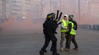 Yellow Vests (Gilets jaunes) protesters stands by riot police forces as they demonstrate against rising oil prices and living costs in Marseille on December 1, 2018. (Photo by Clement MAHOUDEAU / AFP)