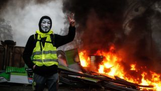 A protester wearing a Guy Fawkes mask makes the victory sign near a burning barricade during a protest of Yellow vests (Gilets jaunes) against rising oil prices and living costs, on December 1, 2018 in Paris. (Photo by Abdulmonam EASSA / AFP)