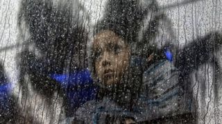 A Central American girl travelling in a migrants' caravan, rides a bus outside a temporary shelter in eastern Tijuana, Baja California state, Mexico, on December 6, 2018. - Thousands of Central American migrants, mostly Hondurans, have trekked for over a month in the hopes of reaching the United States. (Photo by Guillermo Arias / AFP)