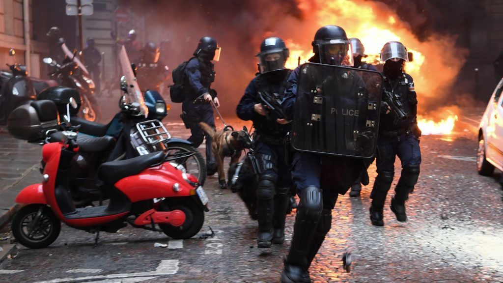 """Riot police run next to a car set on fire during a protest of Yellow vest (Gilet Jaune) against rising costs of living they blame on high taxes on December 8, 2018 on the Champs-Elysees avenue in Paris. - Paris was on high alert on December 8 with major security measures in place ahead of fresh """"yellow vest"""" protests which authorities fear could turn violent for a second weekend in a row. (Photo by Eric FEFERBERG / AFP)"""