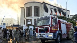 A picture taken on December 25, 2018 shows a firetruck and security officers at the scene of an attack outside the Libyan foreign ministry headquarters in the capital Tripoli. - At least one person was killed on December 25 as attackers stormed Libya's foreign ministry after a car bomb exploded in front of the building and a suicide bomber then struck inside, a security source at the scene told AFP. (Photo by Mahmud TURKIA / AFP)