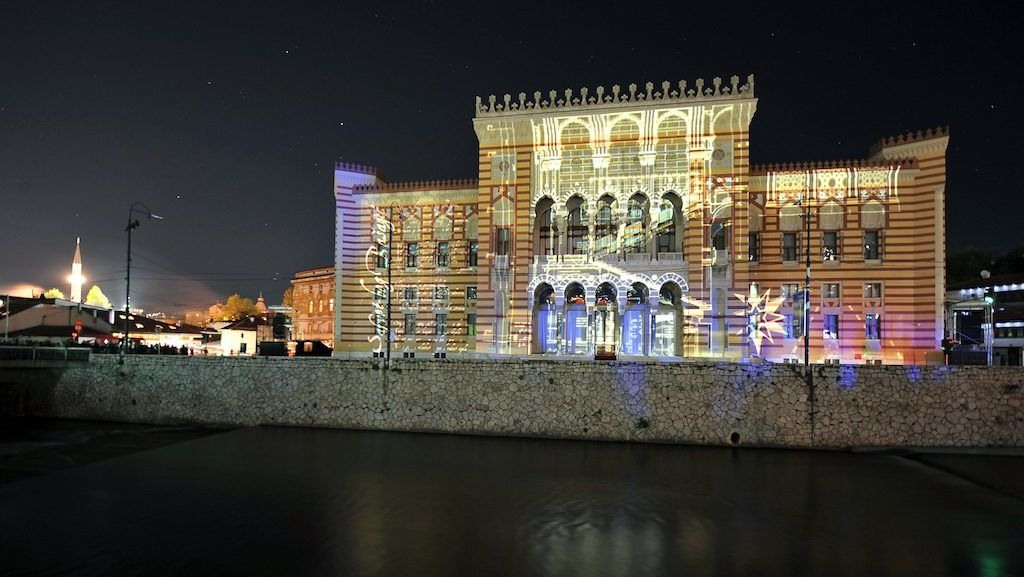 A picture shows the facade of Sarajevo City Hall and National Library building lit with 3D mapping animations during a grand re-opening ceremony, on May 9, 2014. Sarajevo City Hall was built in 1896 while Bosnia was under Austro-Hungarian rule (1878-1914) and was re-purposed into National Library after World War II. It used to contain more than 2 millions of books and artifacts before it was destroyed in a fire caused by mortar and artillery shells fired from Bosnian Serb postions overlooking the city, in the night between August 25-26, 1992. Only some 300.000 pieces of the material were saved from the flames. The building was under reconstruction, mostly founded by the EU, since 1996. AFP / PHOTO ELVIS BARUKCIC (Photo by ELVIS BARUKCIC / AFP)