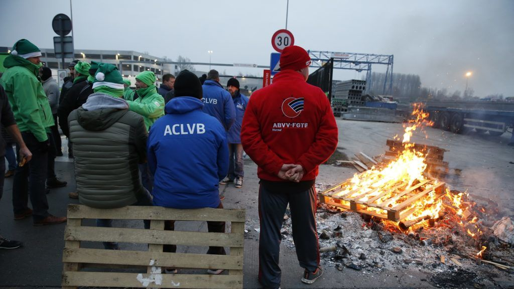 Workers built a fire during a strike organised by unions to protest against the working conditions, including the pension reforms of the federal government, in front of Delhaize distribution center in Ninove, Friday 14 December 2018. BELGA PHOTO NICOLAS MAETERLINCK