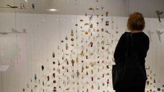 """30 November 2018, Berlin: A visitor stands in front of 250 figures in the exhibition """"Angels, Swastika, Dome of the Rock - Christmas tree decorations from the 19th century to the present day"""" in the German Historical Museum, which together form a Christmas tree. The exhibition is open until 3 March 2019. Photo: Jörg Carstensen/dpa"""