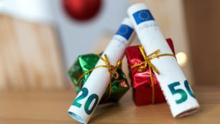 04 December 2018, Saxony, Dresden: ILLUSTRATION - Gift wrapped 20 and 50 Euro banknotes are lying on a table. Photo: Monika Skolimowska/dpa-Zentralbild/ZB