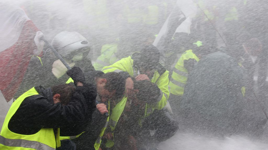 PARIS, FRANCE - DECEMBER 01: Police officers intervene yellow vest protesters with tear gas as they gather to protest against rising fuel taxes near Arc de triomphe de l'Etoile in Paris, France on December 01, 2018. ELYXANDRO CEGARRA / Anadolu Agency
