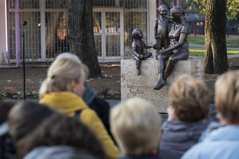 Budapest, 2018. november 13. Koncz Viktória Éva szobrászművész a kisgyermeket nevelők tiszteletére készített, egy fiatal nő és két kisgyermek alakját formázó alkotása az avatóünnepségen, az újpesti Király utcában 2018. november 13-án. MTI/Mónus Márton