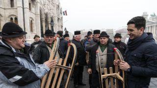 Budapest, 2018. december 21. A Gyimes Völgye Férfikórus tagjai az Ország Karácsonyfájánál a Kossuth téren 2018. december 21-én. A kórus tagjai tíz szánkót hoztak, hogy részben pótolják a december közepén tartott tüntetésen ellopott, megrongált - rászoruló gyermekeknek szánt - sporteszközöket. Az Ország Karácsonyfája körül - immár hagyományosan - 120 szánkóból álló kerítést állítottak fel. MTI/Szigetváry Zsolt