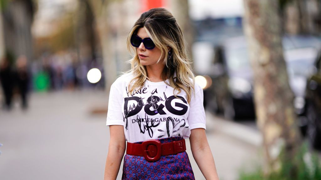 PARIS, FRANCE - SEPTEMBER 28:  A guest wears a burgundy belt, a D&G logo white t-shirt from Dolce & Gabbana, a purple glitter skirt, sunglasses, outside Issey Miyake, during Paris Fashion Week Womenswear Spring/Summer 2019, on September 28, 2018 in Paris, France.  (Photo by Edward Berthelot/Getty Images)