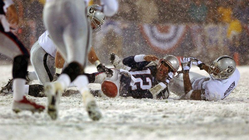 FOXBOROUGH, MA - JANUARY 19: Patriots quarterback Tom Brady loses the ball after being hit by the Oakland Raiders Charles Woodson, right, the fumble was recovered by Greg Biekert, left, but it was ruled an incomplete pass, giving the Patriots another chance. (Photo by Jim Davis/The Boston Globe via Getty Images)