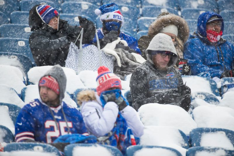 ORCHARD PARK, NY - DECEMBER 10:  Buffalo Bills fans bundled in winter apparel watch action between the Buffalo Bills and the Indianapolis Colts as snow falls at New Era Field on December 10, 2017 in Orchard Park, New York.  Buffalo defeats Indianapolis in overtime 13-7. (Photo by Brett Carlsen/Getty Images) *** Local Caption ***