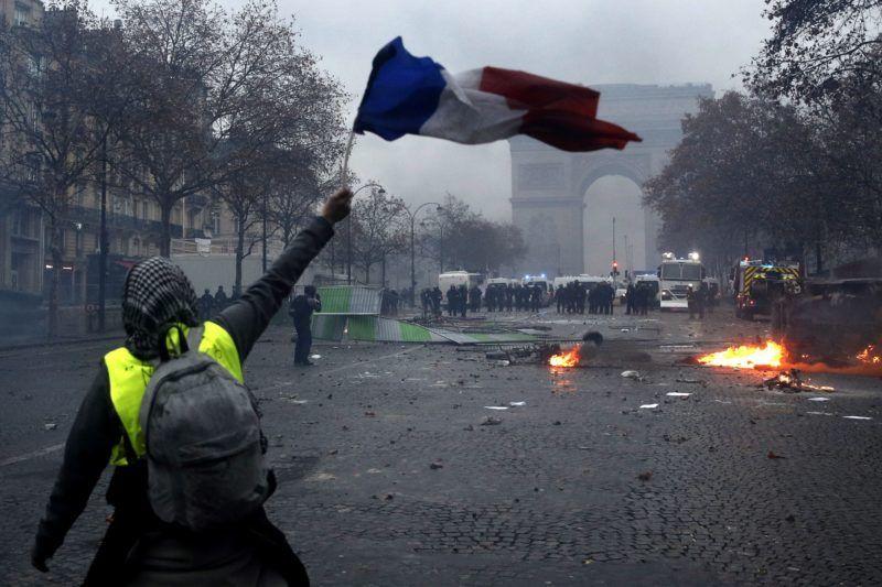 Párizs, 2018. december 2. Francia zászlót lenget a dráguló üzemanyagárak ellen tiltakozó sárga láthatósági mellényt viselõ tüntetõk egyike égõ úttorlaszok elõtt a Diadalív közelében, a párizsi Champs-Elysées sugárúton 2018. december 1-jén. MTI/EPA/Yoan Valat