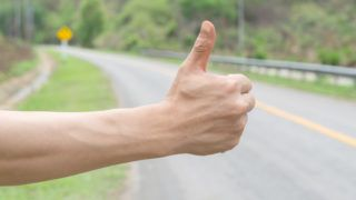 hand and hitchhiking sign on road