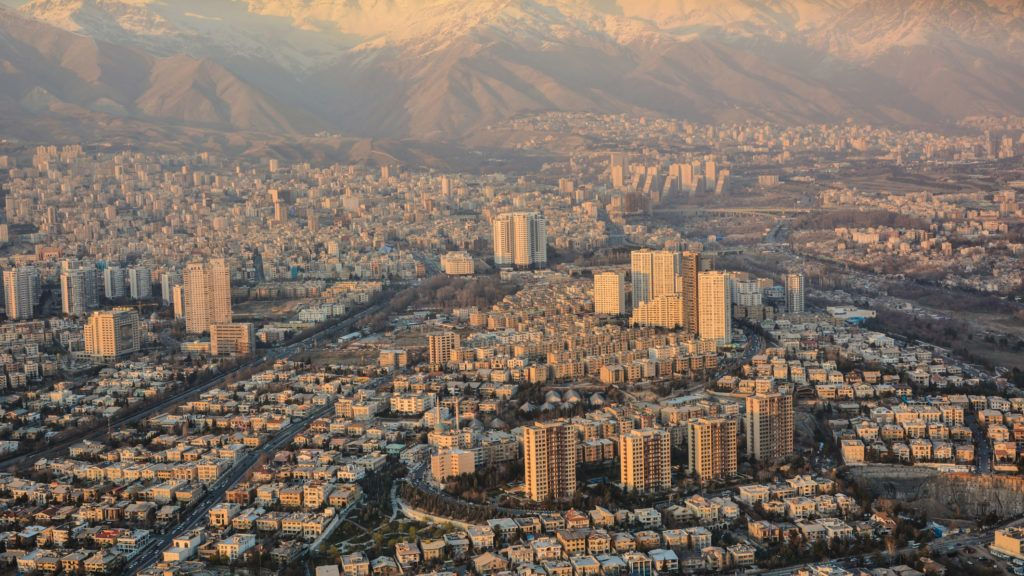 Snowy Alborz Mountain Chain and the sunlight decorate the landscape of smoggy Tehran- taken from Milad Tower in Tehran, Iran