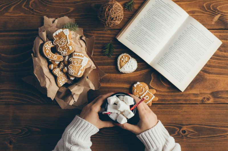 Woman sitting, reading a book, eating Christmas cookies and drinking hot chocolate. Top view