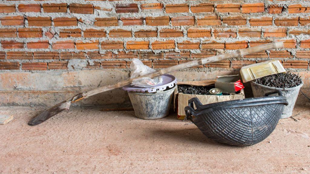 Construction tools put on concrete floor near brick wall under construction.