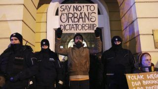 """Varsó, 2018. december 19. """"Mondj nemet Orbán diktatúrájára!"""" feliratú transzparenssel áll egy tüntetõ rendõrök gyûrûjében a varsói magyar nagykövetség elõtt 2018. december 19-én. Tüntetõk egy kis csoportja demonstrációval vállal szolidaritást a Magyarországon az önkéntes túlmunka idõ bõvítésérõl szóló törvény ellen napok óta tiltakozókkal. MTI/AP/Czarek Sokolowski"""