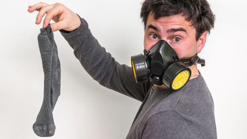 Man with gas mask is holding stinky sock - unpleasant smell concept