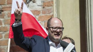 Mayor of Gdansk Pawel Adamowicz flashes the sign of victory as he gives a speech in front of people taking part in an antifascist demonstration on April 21, 2018 in Gdansk, Poland. (Photo by Simon Krawczyk / AFP)