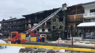 Firefighters and French gendarmes stand in front of a building destroyed by a major fire which killed two people and injured 22 more, on January 20, 2019 at the ski resort of Courchevel in the French Alps. - The pre-dawn blaze forced the evacuation of some 60 resort workers, including foreigners, from a three-storey accommodation building. Firemen found the two unidentified bodies in a burnt-out area of the building in the upmarket Courchevel 1850 ski station. (Photo by Fanny HARDY / AFP)