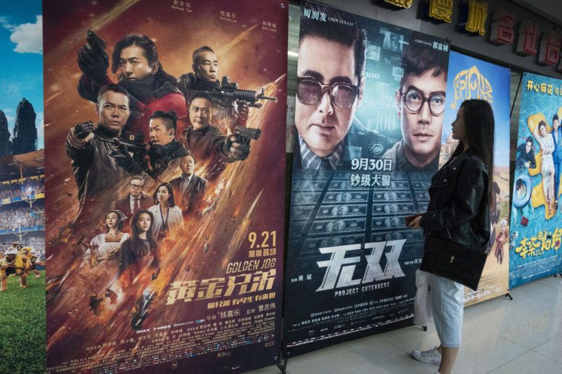 """--FILE--A Chinese moviegoer looks at a poster of Hong Kong action film """"Project Gutenberg"""" at a cinema in Shanghai, China, 11 October 2018.China has seen a total box office revenue of more than 52.6 billion yuan (7.62 billion U.S. dollars) during the first 10 months of 2018, up 9.75 percent year-on-year, according to the State Film Administration. Domestic films contributed to about 70 percent of the total box office in the period, up 37.56 percent on a yearly basis. Among the 67 films that took in over 100 million yuan, 38 were domestic. In Chinese film market this year, the audience were presented with domestic blockbusters such as black comedy """"Dying to Survive,"""" comedy """"Detective Chinatown 2"""" and action film """"Operation Red Sea,"""" which all grossed over 3 billion yuan in box office. In November and December, more domestic productions, including """"The Human Comedy"""" and """"The Rookies"""", are scheduled to hit the big screen alongside Hollywood blockbusters such as anti-hero action-thriller """"Venom"""" and """"Fantastic Beasts: The Crimes of Grindelwald."""""""