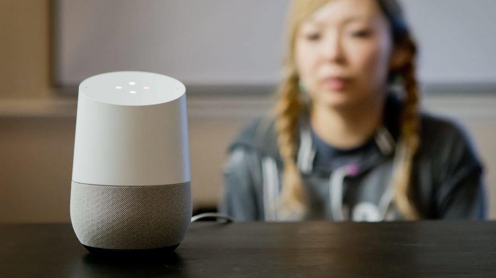Woman interacting with a Google Home smart speaker in a living room in California, in February 2018. | usage worldwide