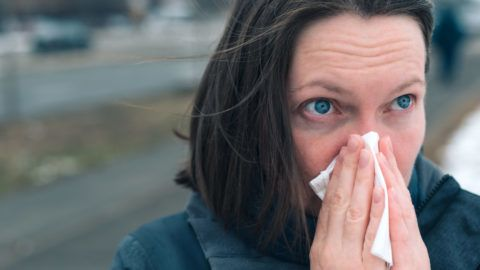 Woman blowing her nose into paper handkerchief out on the street on a cold winter day at the start of the flu season