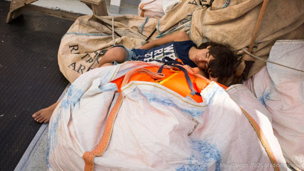 """A handout photo released on September 25, 2018 by SOS Mediterranee shows a rescued migrant sleeping at the Aquarius rescue ship run by non-governmental organisations (NGO) """"SOS Mediterranee"""" and """"Medecins Sans Frontieres"""" (Doctors without Borders) in the search and rescue zone off the coast of Libya, in the Mediterranean Sea. - The 58 migrants aboard the Aquarius rescue ship will be taken to Malta and from there to France, Germany, Portgual and Spain, after a deal was reached to defuse the latest row over the fate of people rescued in the Mediterranean. (Photo by Maud VEITH / SOS MEDITERRANEE / AFP) / RESTRICTED TO EDITORIAL USE - MANDATORY CREDIT """"AFP PHOTO /SOS MEDITERRANEE / Maud VEITH """" - NO MARKETING NO ADVERTISING CAMPAIGNS - DISTRIBUTED AS A SERVICE TO CLIENTS"""