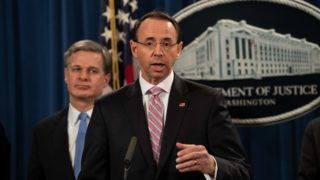 """US Attorney General Rod Rosenstein speaks at a press conference about Chinese hacking as FBI Director Christopher Wray looks on at the Justice Department in Washington, DC, on December 20, 2018. - The US Justice Department on Thursday announced fresh indictments of Chinese government hackers who allegedly targeted scores of companies in a dozen countries, which US officials said showed Beijing had not fulfilled its pledge to stop such actions. In an operation coordinated with US allies in Europe and Asia, Deputy Attorney General Rod Rosenstein said the move was being made to rebuff """"China's economic aggression."""" (Photo by NICHOLAS KAMM / AFP)"""