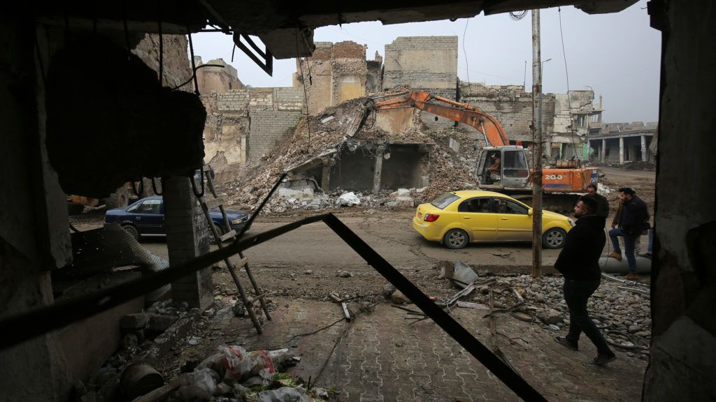 An Iraqi man destroys a building with an excavator as people start to rebuild their houses in the old city of Mosul on December 23, 2018. (Photo by AHMAD AL-RUBAYE / AFP)
