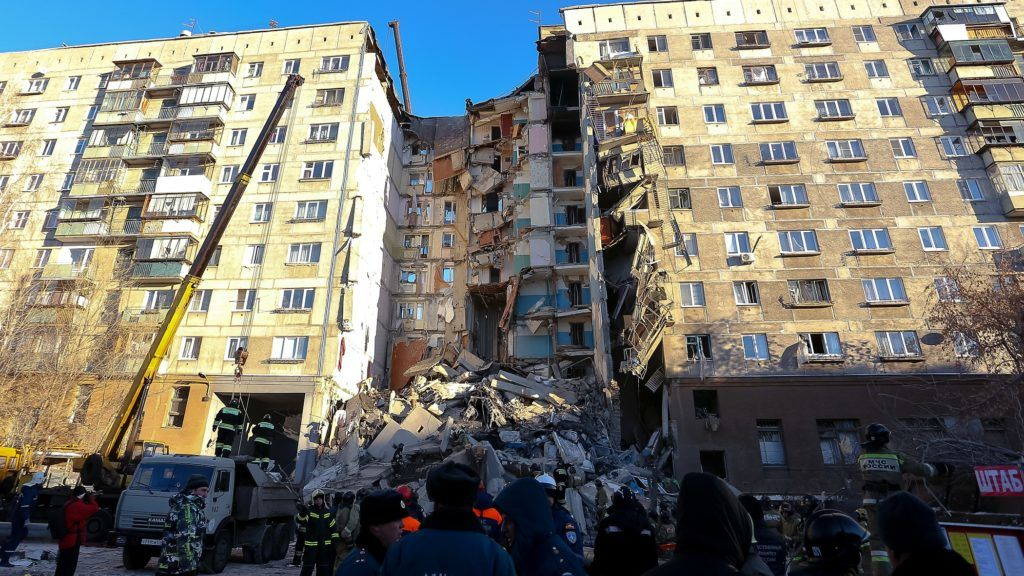 Emergency officers take part in a rescue operation after a gas explosion rocked a residential building in Russia's Urals city of Magnitogorsk on December 31, 2018. - At least 4 dead after gas explosion in residential building in Russia. (Photo by STR / AFP)