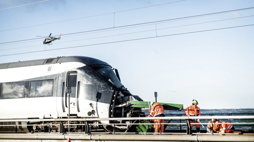 Men work at the accident site next to a passenger train standing on the rails in Nyberg, Denmark, after the Great Belt Bridge was closed following a railway accident on January 2, 2019. - Six people were killed in a train accident on a bridge connecting two islands in Denmark, rail operator DSB said. The accident occurred on the Great Belt Bridge connecting the islands of Zealand, where Copenhagen is located, and Funen. (Photo by Tim K. Jensen / Ritzau Scanpix / AFP) / Denmark OUT