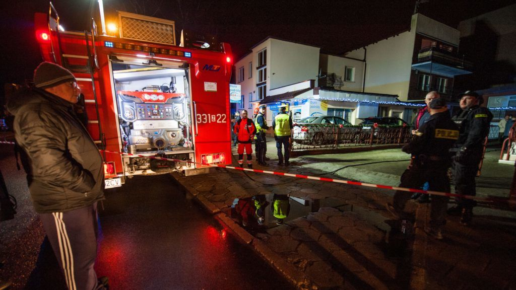 Police and firefighters stand in front of a place, where a fire that broke out in an escape room killed five teenage girls, in the northern Polish city of Koszalin on January 4, 2019. - Five teenage girls died and one man was seriously injured on January 4 when a fire broke out in a room where they were playing an escape game in the northern Polish city of Koszalin, officials said. Police and fire officials said they did not yet know what started the blaze in the escape room, which was reported in the early evening. (Photo by Radoslaw Kolesnik / REPORTER / AFP) / Poland OUT