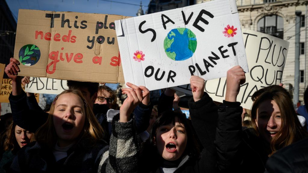 """Students show placard reading """"Save our planet"""" in a protest against climate during a strike on January 18, 2019 in Lausanne. - Thousands of school students take part in the strike across Switzerland on January 18, 2019 to protest against climate change, inspired by Swedish youth activist Greta Thunberg. (Photo by Fabrice COFFRINI / AFP)"""