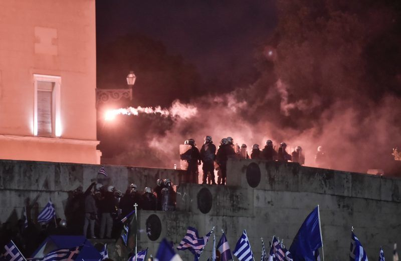 Riot police stand guard outside the Greek parliament as protesters throw flares during a demonstration against an agreement to rename Greece's neighbour Macedonia as the Republic of North Macedonia in Athens on January 24, 2019. - Greece's parliament, on January 24, postponed for several hours a historic vote on a deal to change the name of neighbouring former Yugoslav Republic as the Republic of North Macedonia and end one of the world's longest diplomatic disputes. (Photo by LOUISA GOULIAMAKI / AFP)