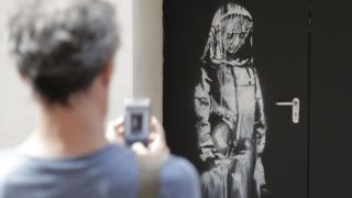 (FILES) In this file photo taken on June 25, 2018, a man takes a photograph of an artwork by street artist Banksy in Paris on a side street to the Bataclan concert hall where a terrorist attack killed 90 people on Novembre 13, 2015. - The artwork by street artist Banksy on a side street to the Bataclan concert hall was stolen in Paris on January 26, 2019. (Photo by Thomas SAMSON / AFP) / RESTRICTED TO EDITORIAL USE - MANDATORY MENTION OF THE ARTIST UPON PUBLICATION - TO ILLUSTRATE THE EVENT AS SPECIFIED IN THE CAPTION