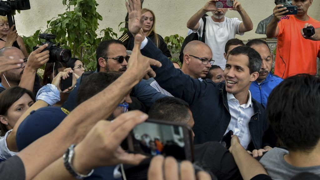 """Venezuela's National Assembly head and self-proclaimed """"acting president"""" Juan Guaido (R) waves at supporters as he leaves after attending a mass in honour to the fallen in the fight for freedom, political prisoners and the exiled, at the San Jose church in Caracas on January 27, 2019. - Guaido, who has galvanized a previously divided opposition, is offering an amnesty approved by the opposition-controlled National Assembly to anyone in the military who disavows President Nicolas Maduro, even suggesting amnesty for Maduro himself. (Photo by Luis ROBAYO / AFP)"""