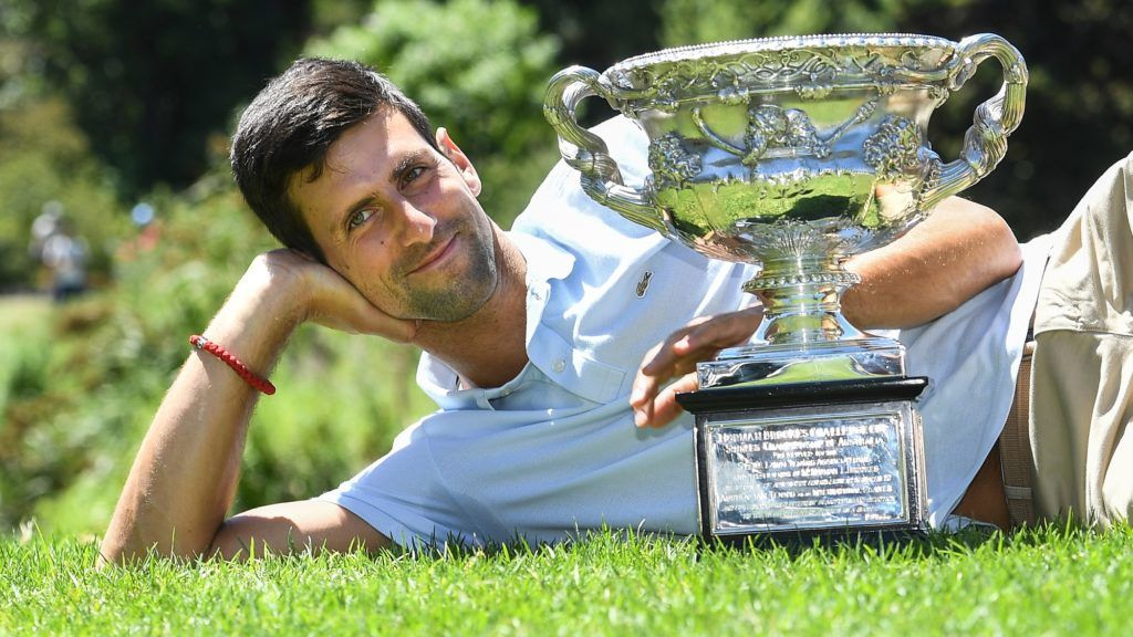 Serbia's Novak Djokovic poses for photographs with the championship trophy at the Royal Botanical Gardens in Melbourne on January 28, 2019, a day after his victory against Spain's Rafael Nadal in the men's singles final of the Australian Open tennis tournament. (Photo by William WEST / AFP) / -- IMAGE RESTRICTED TO EDITORIAL USE - STRICTLY NO COMMERCIAL USE --
