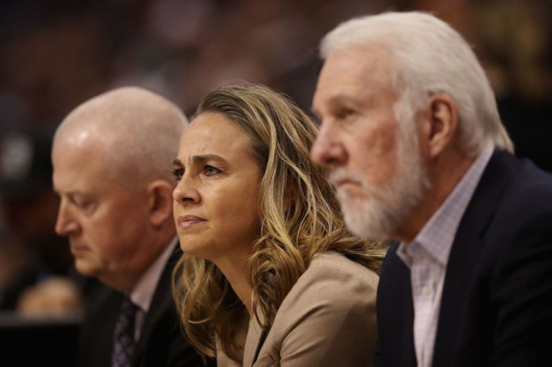 PHOENIX, AZ - NOVEMBER 14:  Assistant coach Becky Hammon (C) of the San Antonio Spurs sits alongside head coach Gregg Popovich (R)during the first half of the NBA game against the Phoenix Suns at Talking Stick Resort Arena on November 14, 2018 in Phoenix, Arizona. NOTE TO USER: User expressly acknowledges and agrees that, by downloading and or using this photograph, User is consenting to the terms and conditions of the Getty Images License Agreement.  (Photo by Christian Petersen/Getty Images)