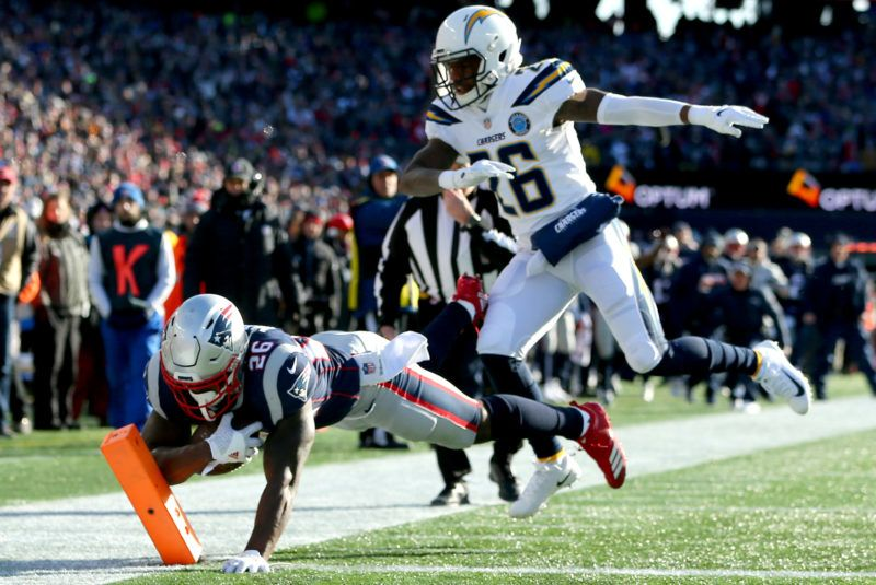 FOXBOROUGH, MASSACHUSETTS - JANUARY 13: Sony Michel #26 of the New England Patriots scores a touchdown as he is defended by Casey Hayward #26 of the Los Angeles Chargers during the first quarter of the AFC Divisional Playoff Game at Gillette Stadium on January 13, 2019 in Foxborough, Massachusetts. (Photo by Adam Glanzman/Getty Images)