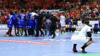 HERNING, DENMARK - JANUARY 27: Jannik Kohlbacher of Germany looks dejected as the players and officials of France celebrate winning at the end during the 26th IHF Men's World Championship 3rd place match between Germany and France at Jyske Bank Boxen Arena on January 27, 2019 in Herning, Denmark. (Photo by Martin Rose/Bongarts/Getty Images)