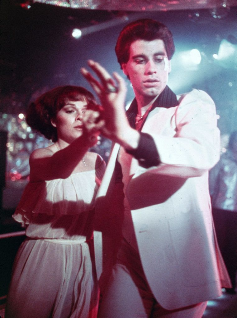 American actors John Travolta, wearing a white suit with a black shirt, and Karen Lynn Gorney disco dance in a still from the film, 'Saturday Night Fever,' directed by John Badham, 1977. (Photo by Fotos International/Courtesy Getty Images)
