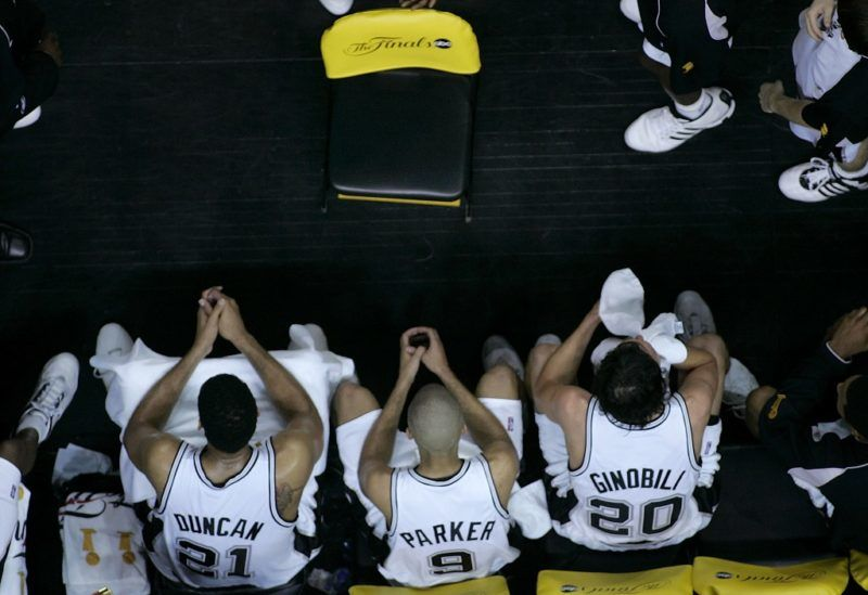 SAN ANTONIO - JUNE 21:  (L-R)  Tim Duncan #21, Tony Parker #9 and Manu Ginobili #20 of the San Antonio Spurs sit on sidelines late in the game during a stoppage in play during Game six of the 2005 NBA Finals at SBC Center on June 21, 2005 in San Antonio, Texas.  NOTE TO USER: User expressly acknowledges and agrees that, by downloading and/or using this Photograph, user is consenting to the terms and conditions of the Getty Images License Agreement  (Photo by Stephen Dunn/Getty Images)