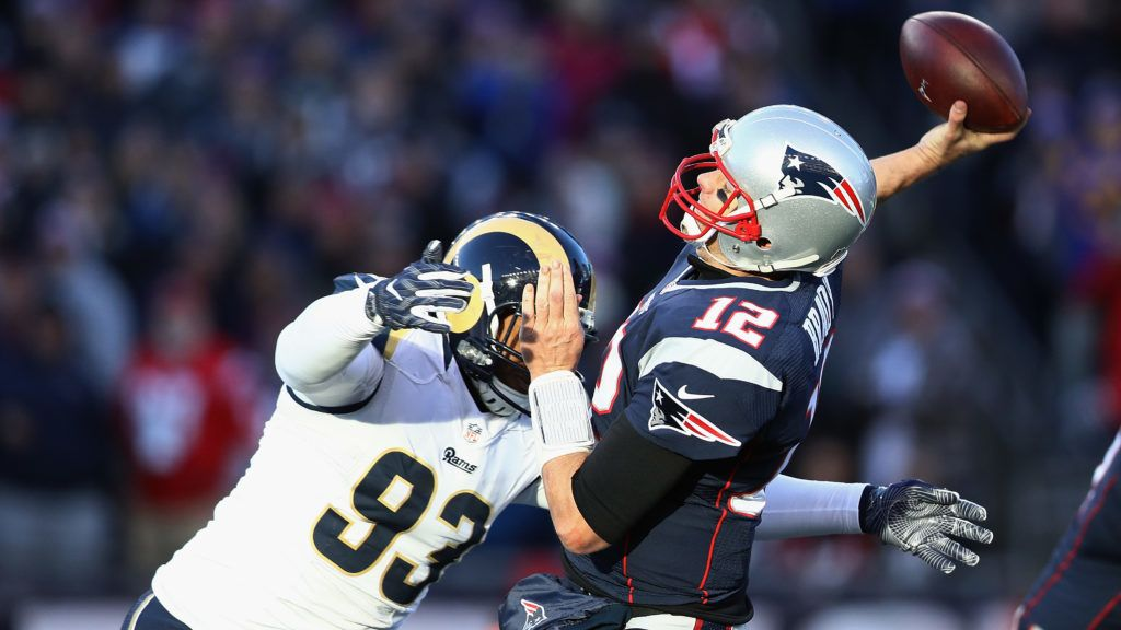 FOXBORO, MA - DECEMBER 04:  Tom Brady #12 of the New England Patriots is hit by Ethan Westbrooks #93 of the Los Angeles Rams during their game at Gillette Stadium on December 4, 2016 in Foxboro, Massachusetts.  (Photo by Maddie Meyer/Getty Images)