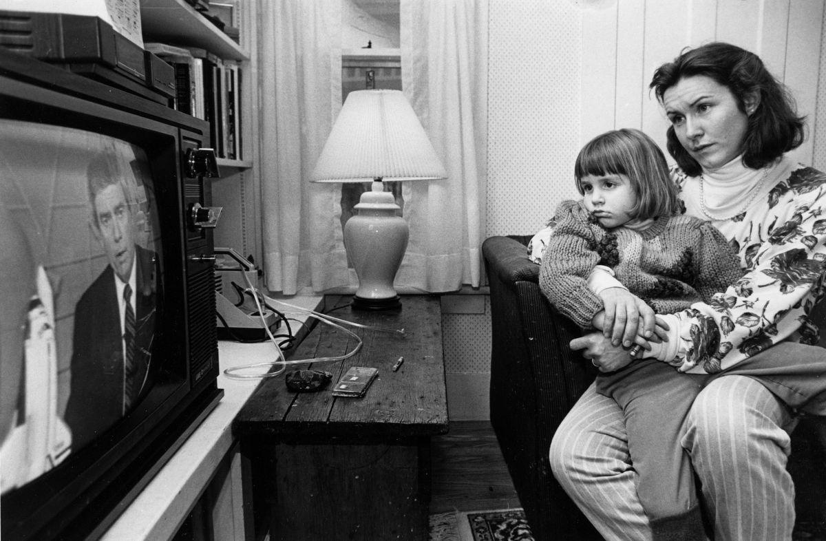 """Mandana Marsh a 4 Žves l‡ny‡t Mollyt a kezŽben tartva figyelik a televizi—ban a katasztr—f‡r—l sz—l— h'reket. Amikor Mandana elmagyar‡zza Mollynak hogy mi tšrtŽnt, a gyerek csak annyit kŽrdezett, hogy """"Christa tud-e œszni?""""Fot—: Suzanne Kreiter / The Boston Globe / Getty Images"""