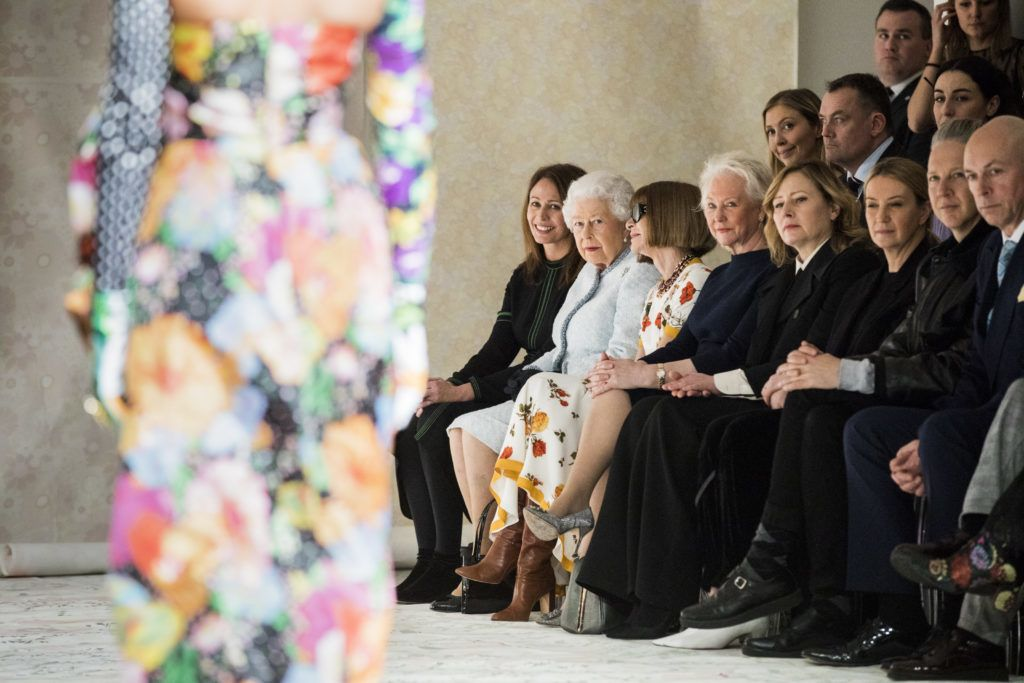 LONDON, ENGLAND - FEBRUARY 20:  Queen Elizabeth II (L), Chief Executive of the British Fashion Council Caroline Rush (C) and Anna Wintour (R) watch model Adwoa Aboah walking the runway at the Richard Quinn show during London Fashion Week February 2018 on February 20, 2018 in London, England.  (Photo by Tristan Fewings/BFC/Getty Images)